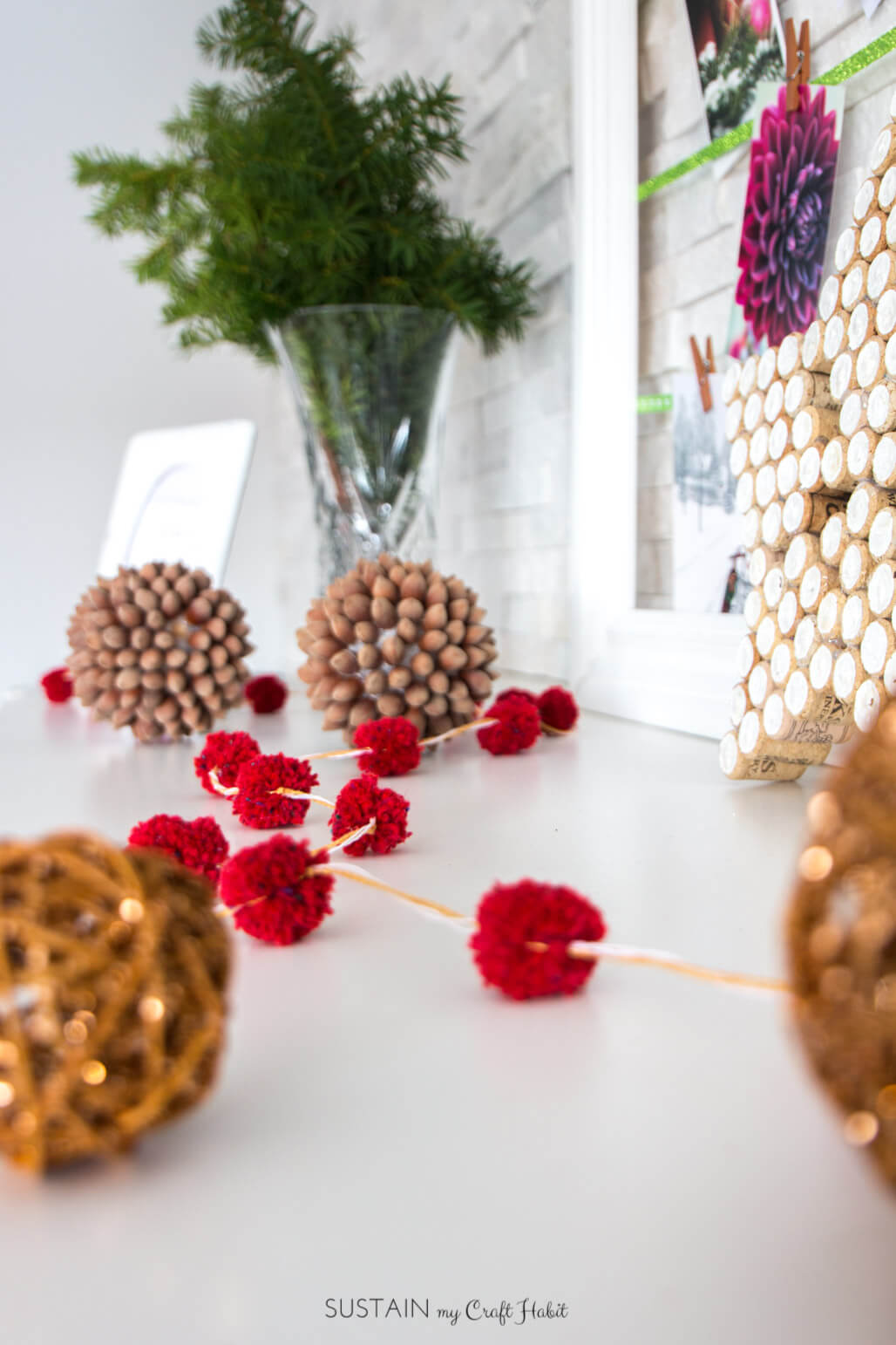 This mini pompom garland from red yarn makes a fun and cute decoration for christmas.