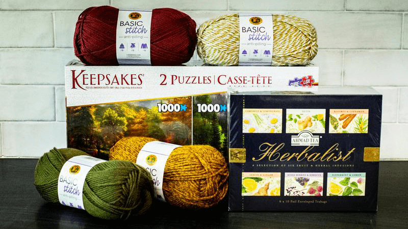 A picture of the Sip, Stitch, Solve gift set from Lionbrand Yarn. Pictured is the Herbalist one, which includes: a 2 puzzle box with nature scenario pictures, one summer and one in fall colors. There are also four skeins of Lionbrand yarn in fall colors, mustard yellow, deep green and red and a mouline yarn in white and golden yellow. At the front is a packet of herbalist tea with pictures of demon, ginger and a bounch of other herbs, berries and fruits on it. The Sip, Stitch, Solve gift sets bought from Lionbrand Yarn are perfect gifts when you want to show that you care. You can choose between Herbalist, Classical, or Fruity set.
