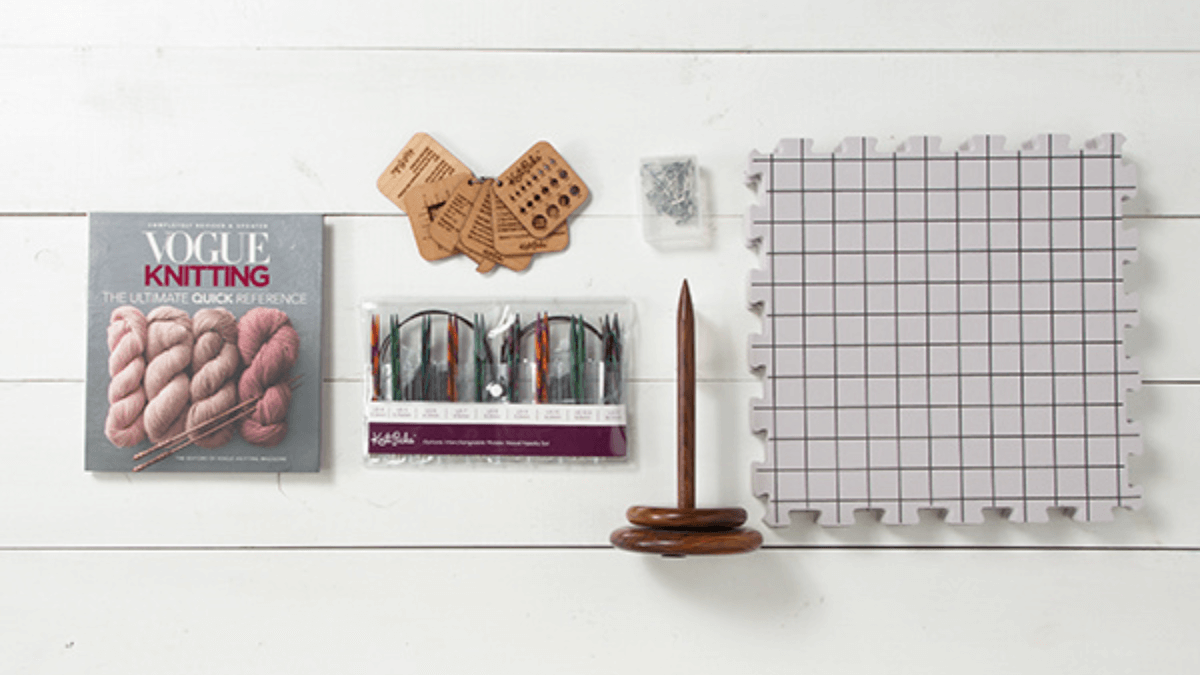 the luxe knitting basics kit from KnitPicks includes a set of beautiful Wooden Interchangeable knitting needles, Vogue Knitting: The Ultimate Quick Reference,  Premium Blocking Mats & T-Pins, a Wood Yarn Spindle, and a Mini Tool Set