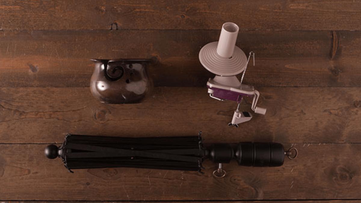 This onyx yarn winding set includes a wooden yarn swift, a yarn ball winder, and a yarn bowl in black mango wood.
